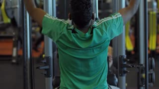 Tilt up with rear view of Arab man in sportswear doing wide-grip front pull-downs on machine in gym