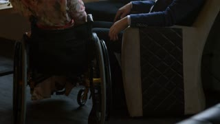 Tilt up with rear view of paraplegic woman in wheelchair and bearded man sitting at table in cafe and holding hands, then drinking red wine and kissing