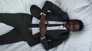 Top view of African-American businessman in suit sleeping in bed, then waking up and laughing as money falling on him from above
