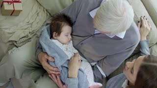 Top view of grandfather with grey hair holding sleeping baby while visiting young mother