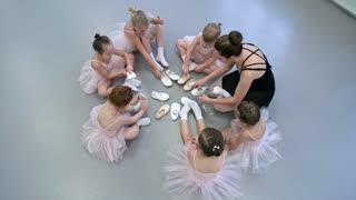 Top view of group of little girls sitting in circle and learning to put on ballet shoes, their teacher helping one of them