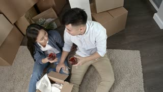 Top view of happy Asian couple sitting on floor and drinking red wine after moving to new house