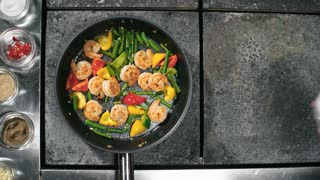 Top view of unrecognizable cook adding soy sauce and water into shrimps and vegetables sizzling in oil, then tossing pan