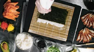 Top view of unrecognizable cook putting cream cheese on sheet of nori seaweed while preparing sushi rolls