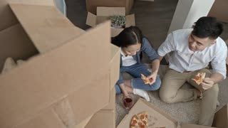 Top view shot of Asian couple sitting on floor and relaxing after hard day of moving house: they eating pizza and drinking red wine