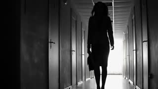 Tracking black and white shot of silhouette of businesswoman with briefcase walking along dark hallway