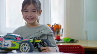 Tracking medium shot of adorable Asian girl smiling at camera and posing with toy car model at school