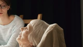 Tracking medium shot of senior woman relaxing in rocking chair and talking to granddaughter or volunteer holding her hand