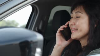 Tracking of mid-aged Asian lady smiling and speaking on mobile phone in driver seat in car
