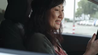 Tracking of mid-aged Asian woman smiling, waving at camera and speaking via video call on smart phone in car