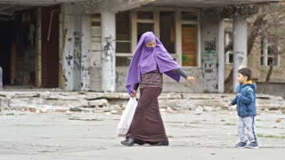 Tracking of Muslim woman in purple niqab holding hands of little boy and girl and walking along street with abandoned building; soldiers with firearms patrolling in background