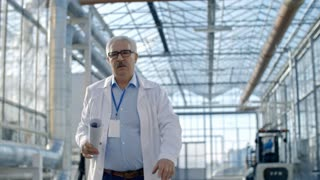 Tracking of senior male agronomist in lab coat and glasses holding sheet of paper and walking through industrial greenhouse complex