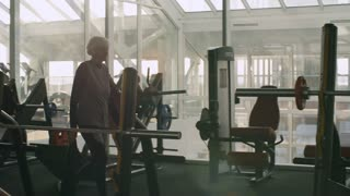 Tracking of tired senior woman with grey hair carrying towel and drinking from sport water bottle while walking in gym after workout