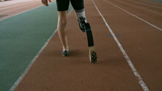 Tracking of unrecognizable runner with prosthetic fitness leg doing jumping exercise on indoor track