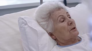 Tracking rack focused shot of elderly woman on hospital bed talking with doctor while saline dripping through IV chamber