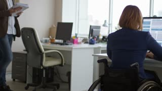 Tracking rear view of disabled businesswoman on wheelchair working on computer at office desk while her male colleague walking with documents