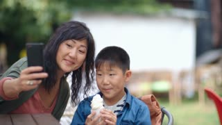 Tracking shot Asian woman smiling at camera of smartphone and taking picture with little son while he eating ice cream in outdoor cafe