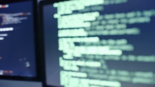 Tracking shot from computer monitors with programming codes to female IT professional discussing something on tablet with male African colleague in the office at night
