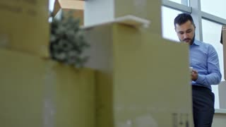 Tracking shot of asian businessman sitting on window sill in new office with stacks of cardboard boxes and making a phone call