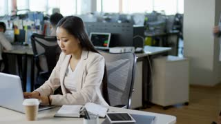 Tracking shot of busy Asian office worker sitting at desk, drinking coffee and writing in notebook when using laptop computer, other people working in the background