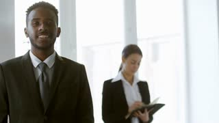 Tracking shot of confident black man in business suit smiling and looking at camera in office, his female colleague standing in the background and writing in notebook
