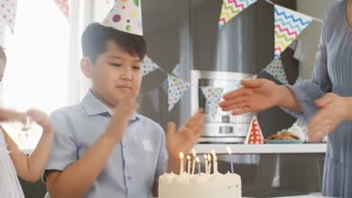 Tracking shot of cute Asian girl in party hat helping her school-age brother blowing out candles on birthday cake as parents clapping