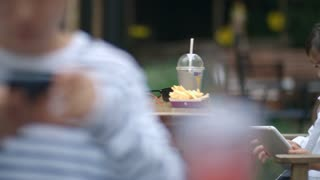 Tracking shot of cute little Asian girl watching something on digital tablet and laughing while sitting at table in outdoor cafe