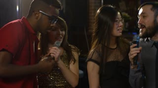 Tracking shot of five multi ethnic young people standing in line in karaoke bar and using microphones to sing to rhythmic music when partying together