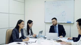 Tracking shot of group of Asian business people having meeting in conference room and laughing at joke