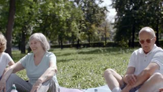 Tracking shot of group of elderly people sitting on yoga mats with their trainer in park, retired man scratching his elbow