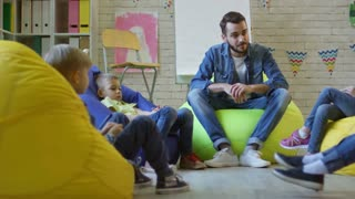Tracking shot of group of little kids sitting on colorful bean bags chairs in kindergarten classroom and talking with young male teacher