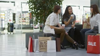Tracking shot of group of three young female friends drinking takeaway coffee and talking when sitting on sofa in shopping center
