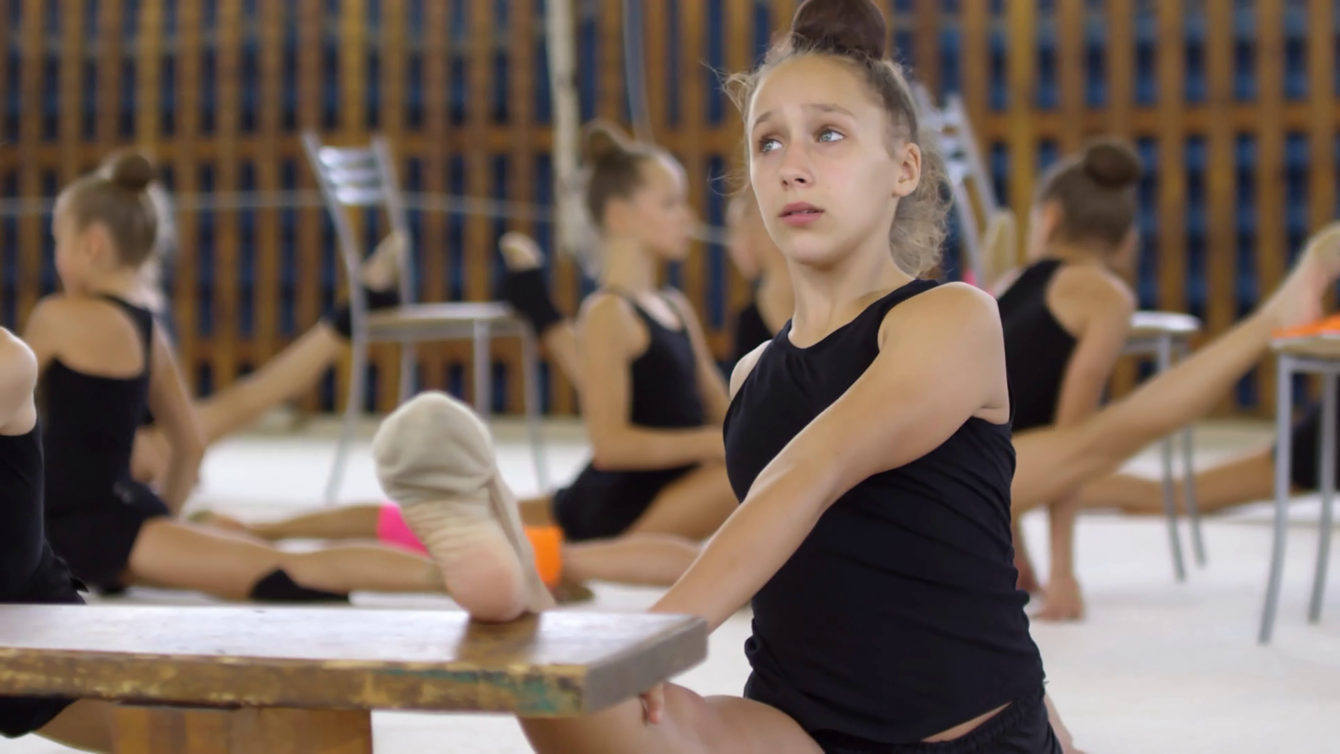 Tracking shot of group of young girls of elementary school age having gymnastics lesson and practicing front splits Stock Video Footage - Storyblocks