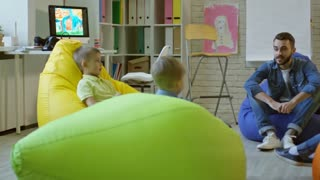 Tracking shot of little boys and girls sitting on colorful bean bags chairs in kindergarten classroom and listening to young male teacher