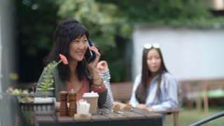 Tracking shot of mid-aged Asian woman sitting at restaurant table outdoors, smiling and talking on cell phone