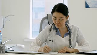 Tracking shot of middle-aged Asian female doctor sitting at desk in her office at clinic, writing down prescription and looking at camera