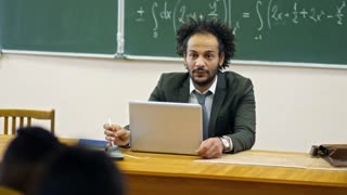 Tracking shot of middle aged curly haired male professor talking to students when sitting in lecture hall at university