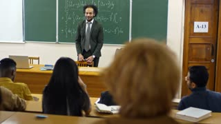 Tracking shot of multi ethnic group of university students seen from their back raising hands to answer teacher's questions during lecture on mathematics
