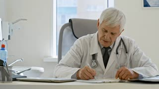 Tracking shot of senior male doctor sitting at desk in the office at clinic, writing down prescription and reading x-ray image
