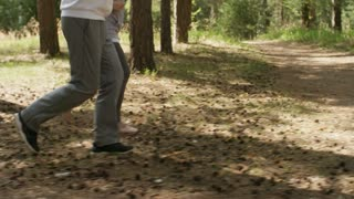 Tracking shot of senior man and woman jogging along forest trail in morning