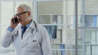 Tracking shot of senior physician with stethoscope speaking on mobile phone in doctor's office