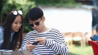Tracking shot of teenage Asian boy and girl sitting at table in outdoor cafe, watching social media post in the Internet, laughing and discussing it