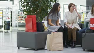 Tracking shot of three happy young women sitting on sofa in shopping mall and showing red gift boxes with presents bought on sale