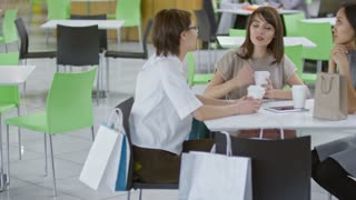 Tracking shot of three young women sitting at table in cafe and talking over cup of coffee after shopping for clothes