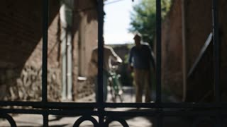 Tracking shot of two elderly male friends, one with walking stick and one with bicycle, approaching camera in narrow way between stone buildings, focus on wrought iron gates before camera