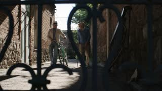 Tracking shot of two senior friends, one with walking stick and one with bicycle, approaching camera in narrow way between stone buildings