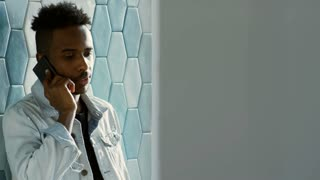 Tracking shot of young African American office worker in casual outfit standing by tile wall in office and speaking on mobile phone