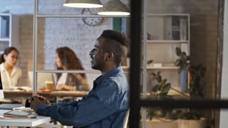 Tracking shot of young african businessman speaking via video call with female colleague in the evening while two women talking behind glass wall in the office