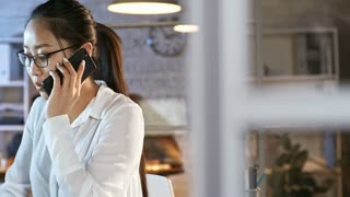 Tracking shot of young asian businesswoman in eyeglasses speaking on mobile phone and using computer while working late in the office