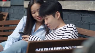 Tracking shot of young Asian couple sitting on bench outdoors, watching something on smartphone, chatting and laughing